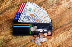 Los billetes de banco cientos dólares en la cartera, bandera americana y differen Foto de archivo