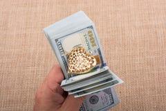 Los billetes de banco del dólar con un corazón acortan en una secuencia Imagen de archivo libre de regalías