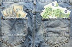 Los billetes de banco del euro y del dólar en parte posterior de los vaqueros embolsan Fotografía de archivo
