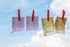 Los billetes de banco euro pesan en la cuerda como lino imagen de archivo libre de regalías