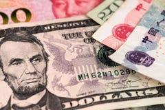 Los billetes de banco de la moneda del dólar americano y de Yuan Renminbi China se cierran encima de imagen USD contra RMB imagen de archivo libre de regalías