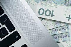 Los billetes de banco polacos acercan al ordenador portátil Foto de archivo