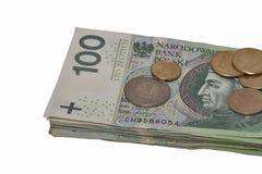 Los billetes de banco polacos apilan y las monedas aisladas en blanco Imagen de archivo