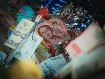 Los billetes de banco de Tailandia 100 que el baht puso en el palillo de madera para donan al budd Imagen de archivo libre de regalías