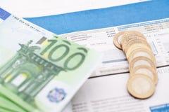 Los billetes de banco y las monedas están en el periódico financiero Foto de archivo libre de regalías