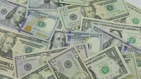 Los billetes de d?lar caen en la tabla con los d?lares americanos de diversas denominaciones almacen de metraje de vídeo