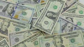 Los billetes de d?lar caen en la tabla con los d?lares americanos de diversas denominaciones almacen de video