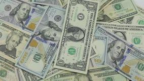 Los billetes de d?lar caen en la tabla con los d?lares americanos de diversas denominaciones metrajes