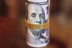 Los billetes de dólar ruedan el dinero con la cadena del oro en la boca de franklin Imagen de archivo