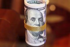Los billetes de dólar ruedan el dinero con la cadena del oro en la boca de franklin Foto de archivo libre de regalías