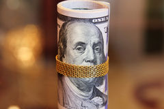 Los billetes de dólar ruedan el dinero con la cadena del oro en la boca de franklin Imagen de archivo libre de regalías
