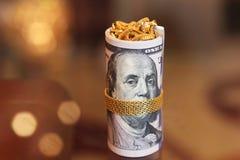 Los billetes de dólar ruedan el dinero con la cadena del oro en la boca de franklin Fotos de archivo libres de regalías
