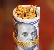 Los billetes de dólar ruedan el dinero con la cadena del oro en la boca de franklin Fotos de archivo