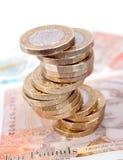 Los billetes y las monedas brit?nicos del dinero apilan foto de archivo