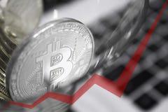 Los bitcoins de oro en un vidrio de cóctel, flecha roja del gráfico se dirigen hacia arriba Foto de archivo libre de regalías
