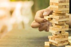 Los bloques de madera apilan el juego, el planeamiento, el riesgo y la estrategia, concepto del fondo del negocio Imagen de archivo