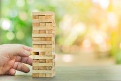 Los bloques de madera apilan el juego, el planeamiento, el riesgo y la estrategia, concepto del fondo del negocio Foto de archivo