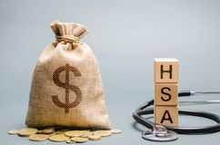 Los bloques de madera con la palabra TIENE y el bolso del dinero con el estetoscopio Cuenta de ahorros de la salud Cuidado médico fotografía de archivo