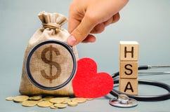 Los bloques de madera con la palabra TIENE y el bolso del dinero con el estetoscopio Cuenta de ahorros de la salud Cuidado médico foto de archivo