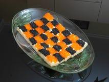 Los bocadillos con el caviar rojo y negro alinearon bajo la forma de tablero de ajedrez Imagenes de archivo