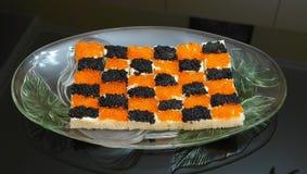 Los bocadillos con el caviar rojo y negro alinearon bajo la forma de tablero de ajedrez Foto de archivo libre de regalías