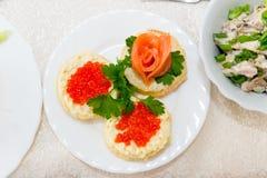 Los bocadillos con el caviar y los salmones rojos se separan en una placa en un cierre de la tabla de comida fría para arriba Fotos de archivo