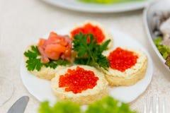Los bocadillos con el caviar y los salmones rojos se separan en una placa en un cierre de la tabla de comida fría para arriba Imagenes de archivo