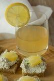Los bocadillos del queso del granjero con la piña y el jugo en de madera plat Foto de archivo
