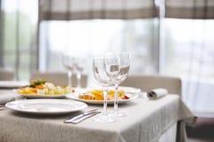 Los bocados y los vidrios para el vino fijaron en restaurante Foto de archivo libre de regalías