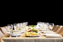 Los bocados y los vidrios para el vino fijaron en restaurante Imagen de archivo libre de regalías