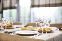 Los bocados y los vidrios para el vino fijaron en restaurante Imagen de archivo