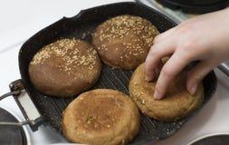 Los bollos hechos en casa frescos para las hamburguesas, fritos en una cacerola, la muchacha las vuelcan imagen de archivo libre de regalías
