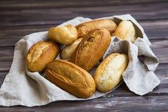 Los bollos recientemente cocidos del pan en una toalla de lino, los bollos del pan entero apilan foto de archivo