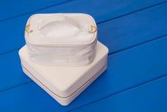 Los bolsos cosméticos blancos están en la tabla azul, bolso del maquillaje, imagen de archivo libre de regalías