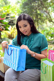 Los bolsos de compras felices de la mujer hermosa de las compras que se sostienen toman resto en el jardín y sonríen Fotografía de archivo