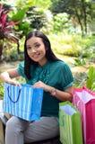 Los bolsos de compras felices de la mujer hermosa de las compras que se sostienen toman resto en el jardín y sonríen Imagen de archivo libre de regalías