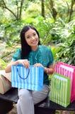 Los bolsos de compras felices de la mujer hermosa de las compras que se sostienen toman resto en el jardín y sonríen Fotos de archivo libres de regalías
