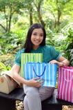 Los bolsos de compras felices de la mujer hermosa de las compras que se sostienen toman resto en el jardín y sonríen Fotos de archivo