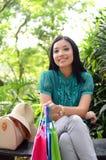 Los bolsos de compras felices de la mujer hermosa de las compras que se sostienen toman resto en el jardín y sonríen Imagenes de archivo