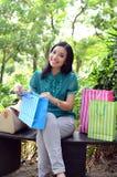 Los bolsos de compras felices de la mujer hermosa de las compras que se sostienen toman resto en el jardín y sonríen Foto de archivo