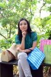 Los bolsos de compras felices de la mujer hermosa de las compras que se sostienen toman resto en el jardín y sonríen Imagen de archivo