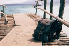 Los bolsos de la mochila pusieron en el suelo en el puente de madera de la costa costa sobre la costa natural azul Foto de archivo