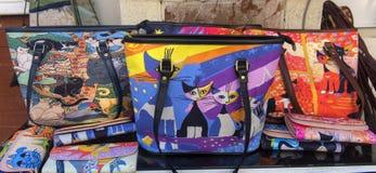Los bolsos de las mujeres con los gatos en una calle almacenan uno de los símbolos de fotos de archivo libres de regalías
