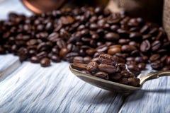 Los bolsos del yute llenaron de café y de la cuchara de plata Foto de archivo libre de regalías