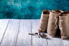 Los bolsos del yute llenaron de café y de la cuchara de plata Imagen de archivo