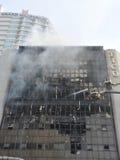 Los bomberos abordan un resplandor en un bloque de oficina Fotos de archivo