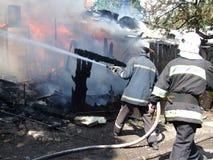 Los bomberos de rociadura del agua del bombero extinguen un fuego en un APAR Fotos de archivo