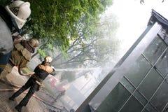 Los bomberos de rociadura del agua del bombero extinguen un fuego en un APAR Foto de archivo