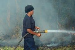 Los bomberos de sexo femenino africanos ayudados a extinguir un fuego del veld del arbusto alegado comenzaron poniendo en cortocir Fotos de archivo libres de regalías
