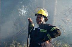 Los bomberos de sexo femenino africanos ayudados a extinguir un fuego del veld del arbusto alegado comenzaron poniendo en cortocir Imagen de archivo